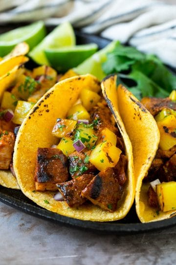 Tacos al pastor stuffed with grilled pork, pineapple, red onion and cilantro.