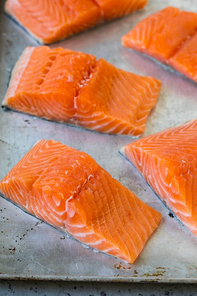 Raw salmon fillets on a sheet pan.