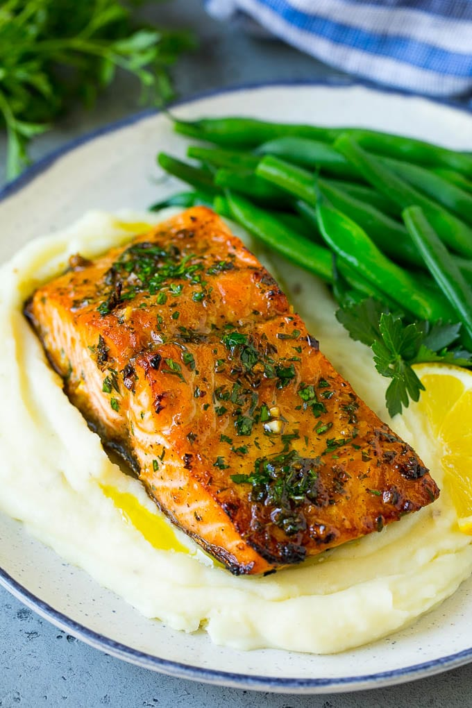 A roasted salmon fillet over mashed potatoes with green beans.