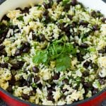 Black beans and rice in a pot topped with cilantro sprigs.