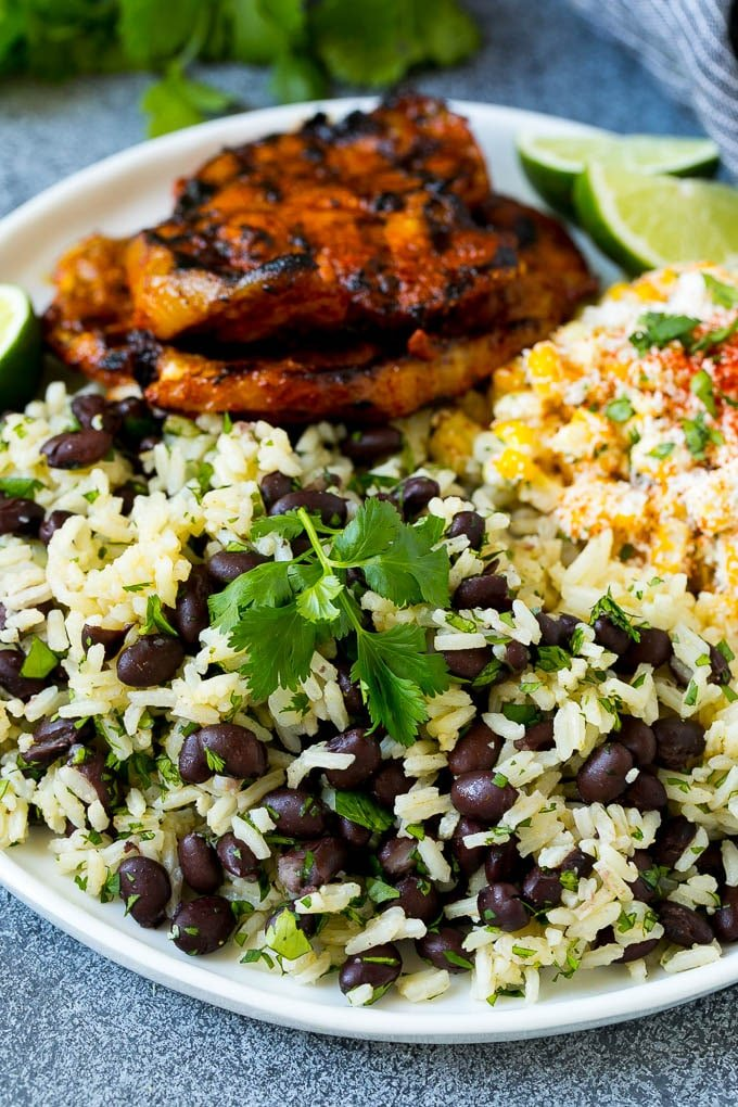 A plate of black beans and rice with grilled pork and Mexican corn.
