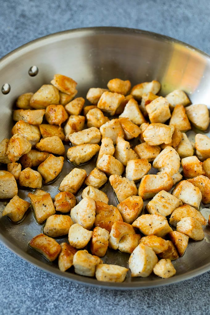 Cooked chicken pieces in a metal pan.