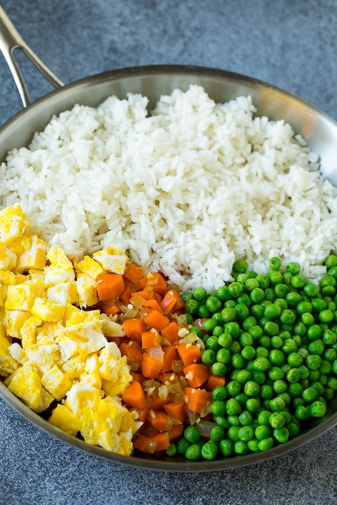 A pan of cooked rice, carrots, eggs and peas.