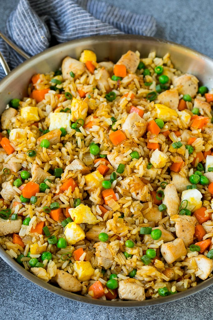 A pan of chicken fried rice with eggs and vegetables.