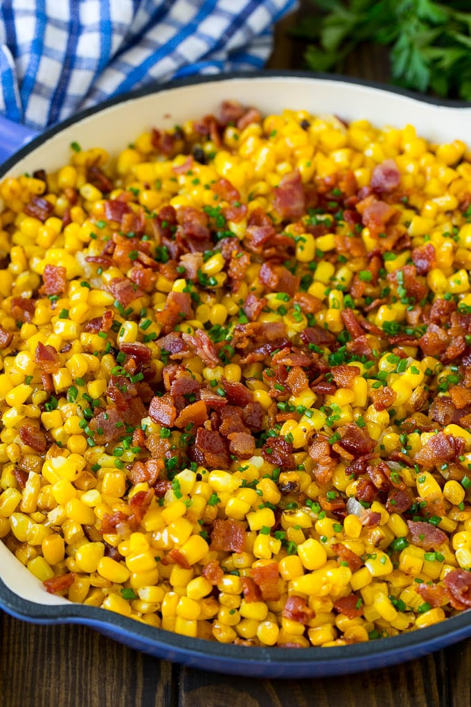 Fried corn topped with bacon and chives in a pan.