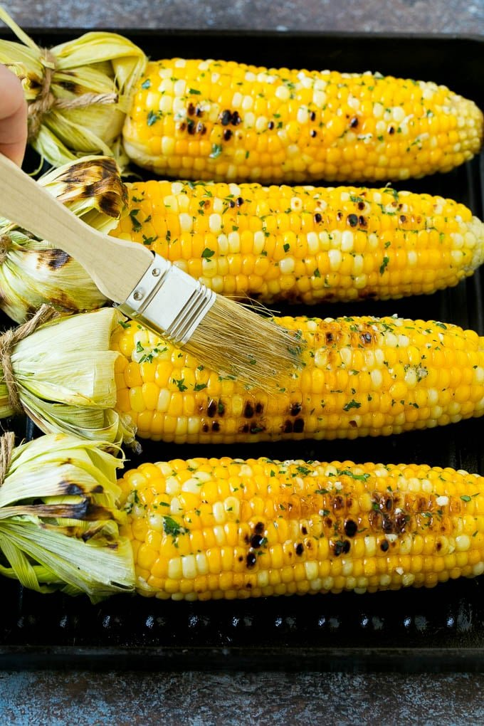 Corn cobs on a grill pan being brushed with herb butter.
