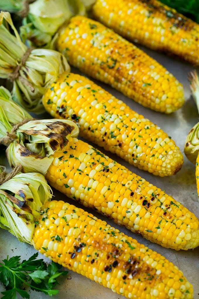 Grilled corn on the cob topped with garlic and herb butter on a sheet pan.