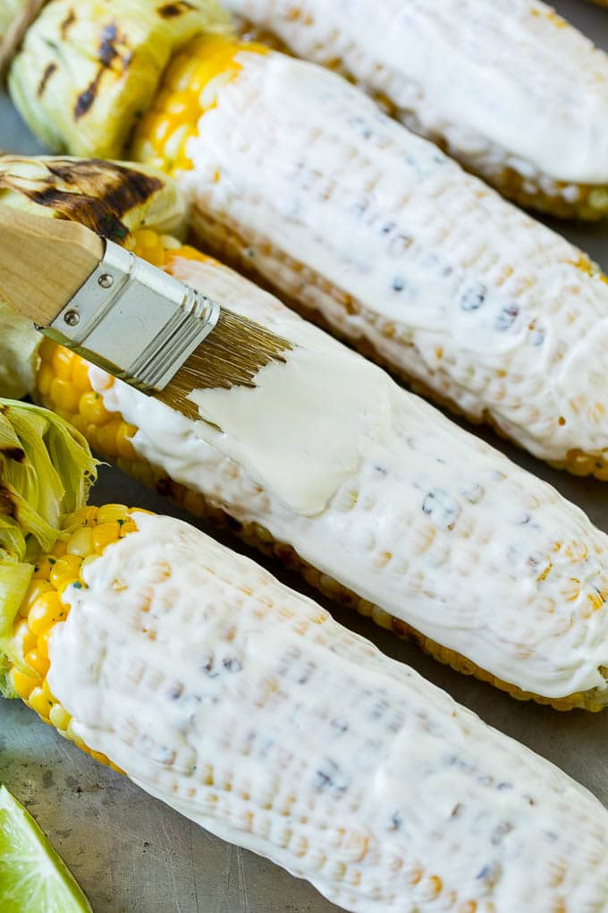 A brush coating corn on the cob with a mixture of mayonnaise and crema.