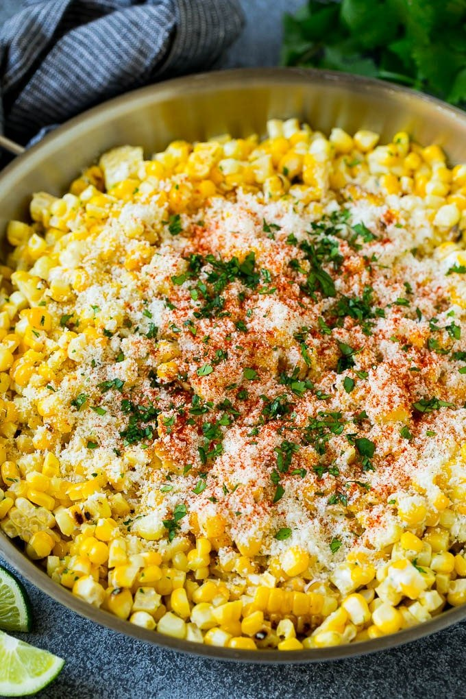 Mexican street corn in a pan topped with cotija cheese, chili power and cilantro.