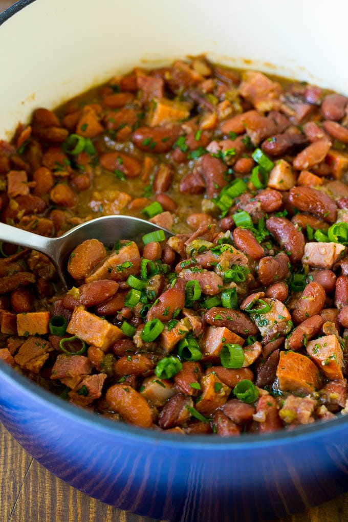 A pot of red beans and rice with sausage, topped with fresh herbs.