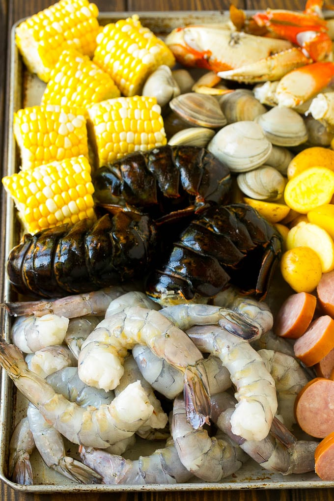 Raw shrimp, lobster, sausage, corn, clams and potatoes on a sheet pan.