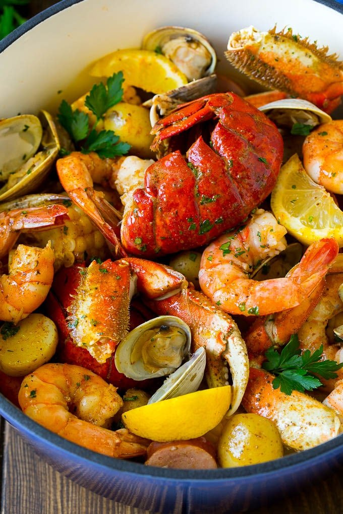 A pot of seafood boil with lobster, shrimp, corn and potatoes.