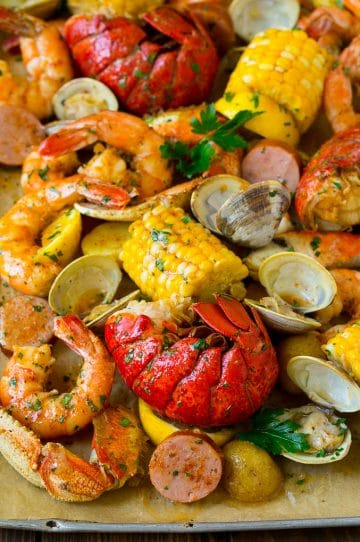 A sheet pan of seafood boil with shrimp, lobster tail, sausage, corn and potatoes.