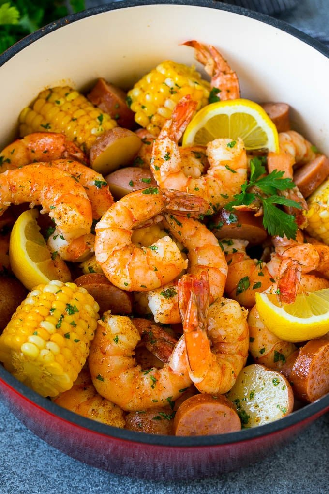 Shrimp boil in a pot garnished with lemon and parsley.