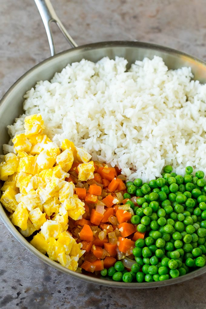 Cooked rice, scrambled eggs, carrots and peas in a pan.