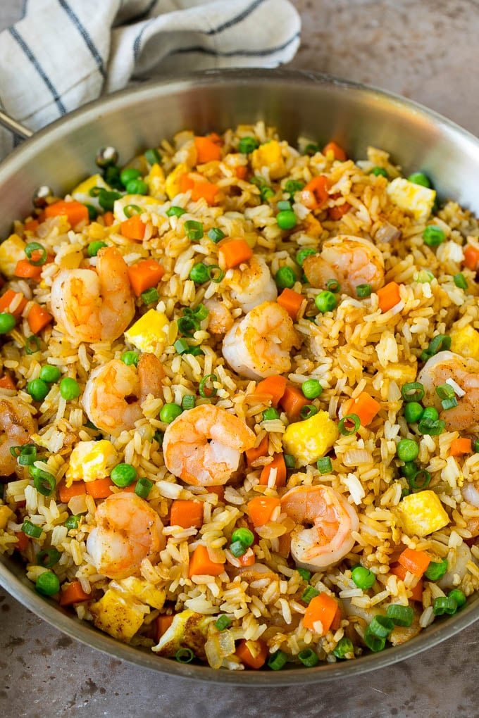 A pan of shrimp fried rice with eggs and vegetables.