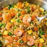 A serving spoon in a pan of shrimp fried rice.