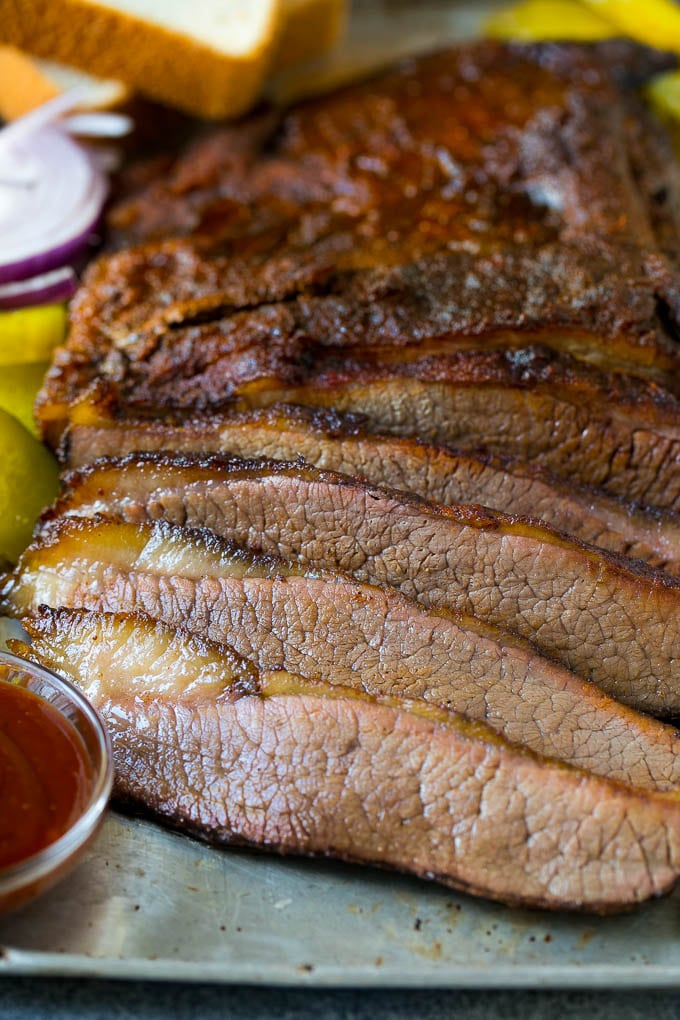 Sliced smoked brisket with a side of BBQ sauce.