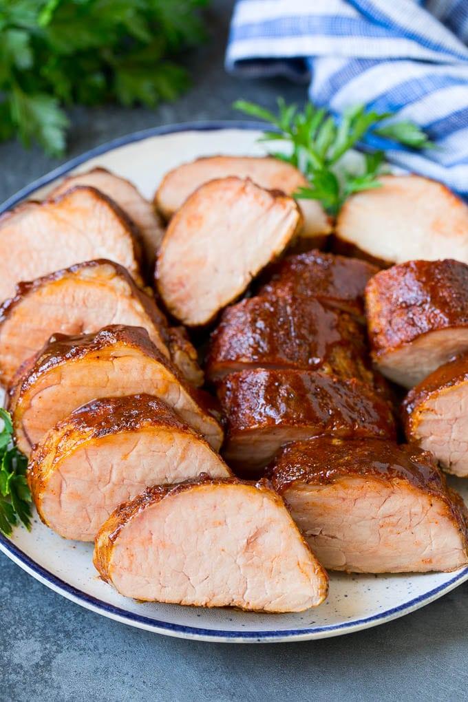 Smoked pork tenderloin sliced on a serving plate.
