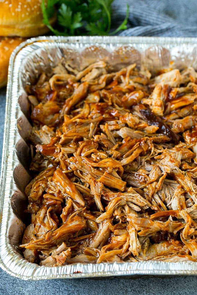 Smoked pulled pork tossed with sauce in a foil pan.