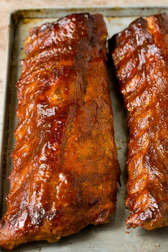 Racks of smoked ribs coated in BBQ sauce.