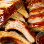 Sliced smoked ribs brushed with BBQ sauce.