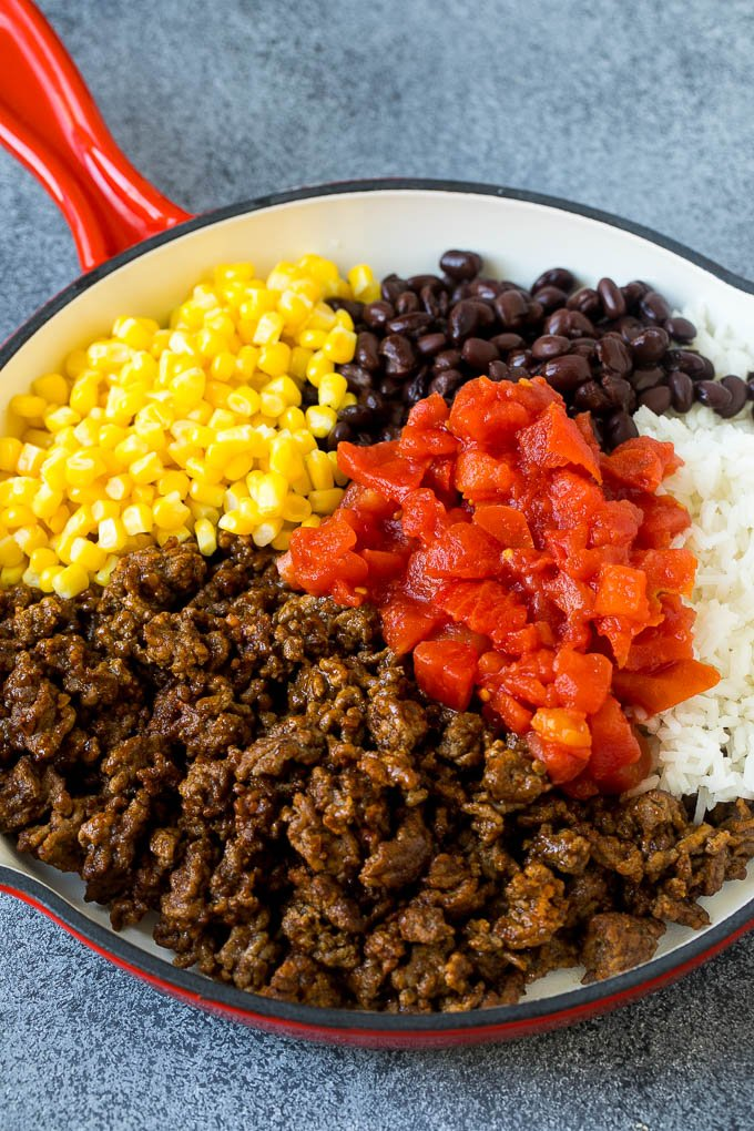 A skillet filled with ground beef, rice, tomatoes, beans and corn.