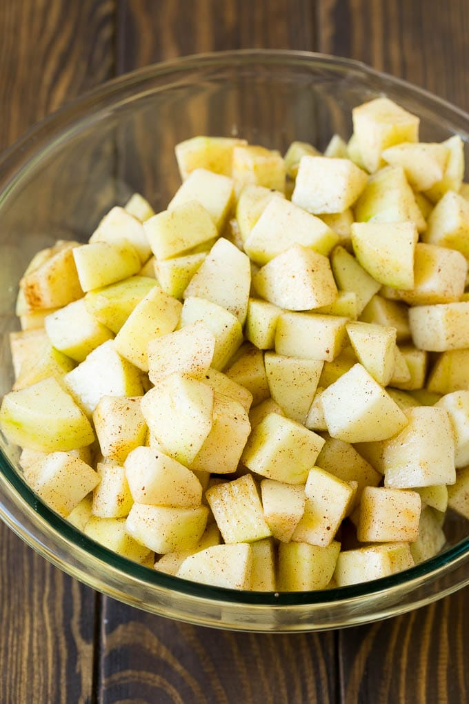 Diced apples tossed with sugar and cinnamon in a bowl.