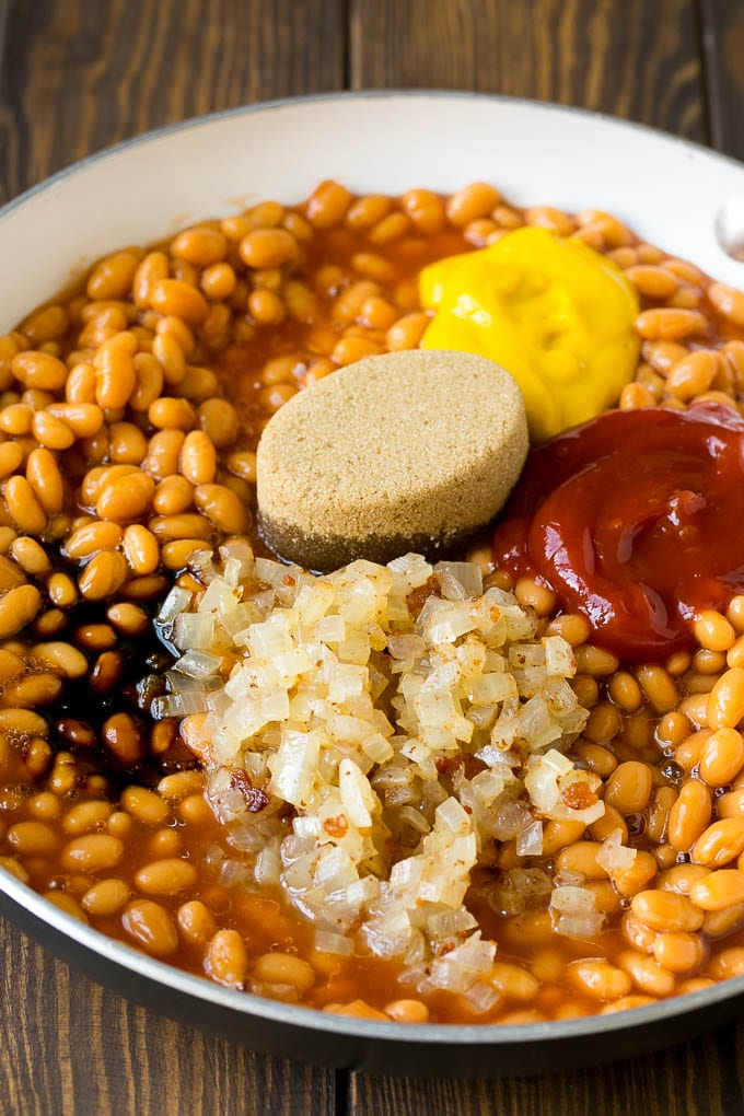 Beans in a pan with onions, molasses, brown sugar, ketchup and mustard.