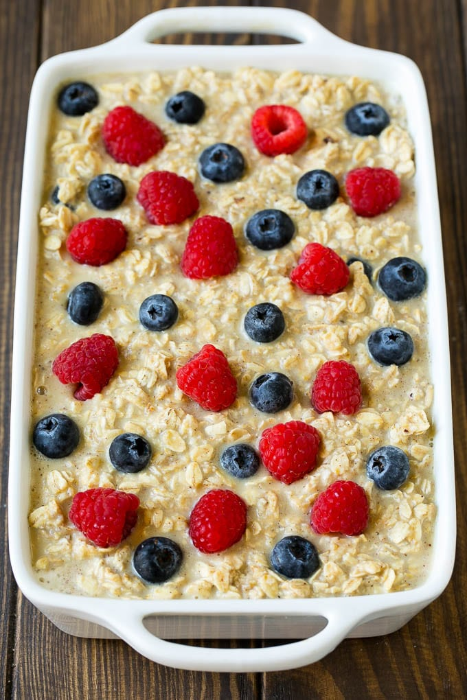 Oatmeal poured into a baking dish with berries on top.