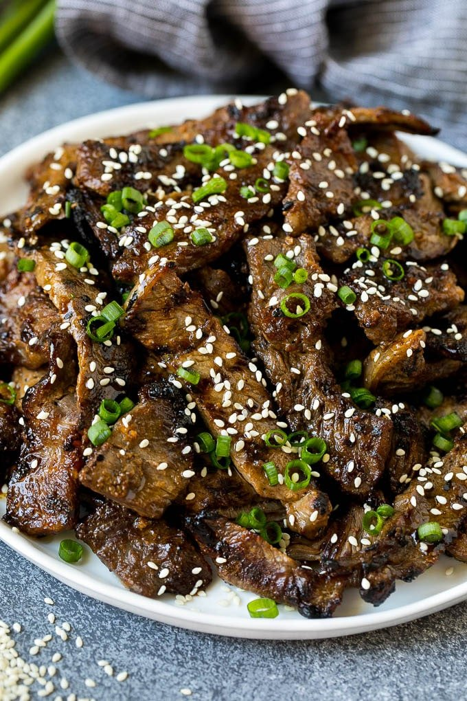 A plate of grilled beef bulgogi topped with sesame seeds and green onions.