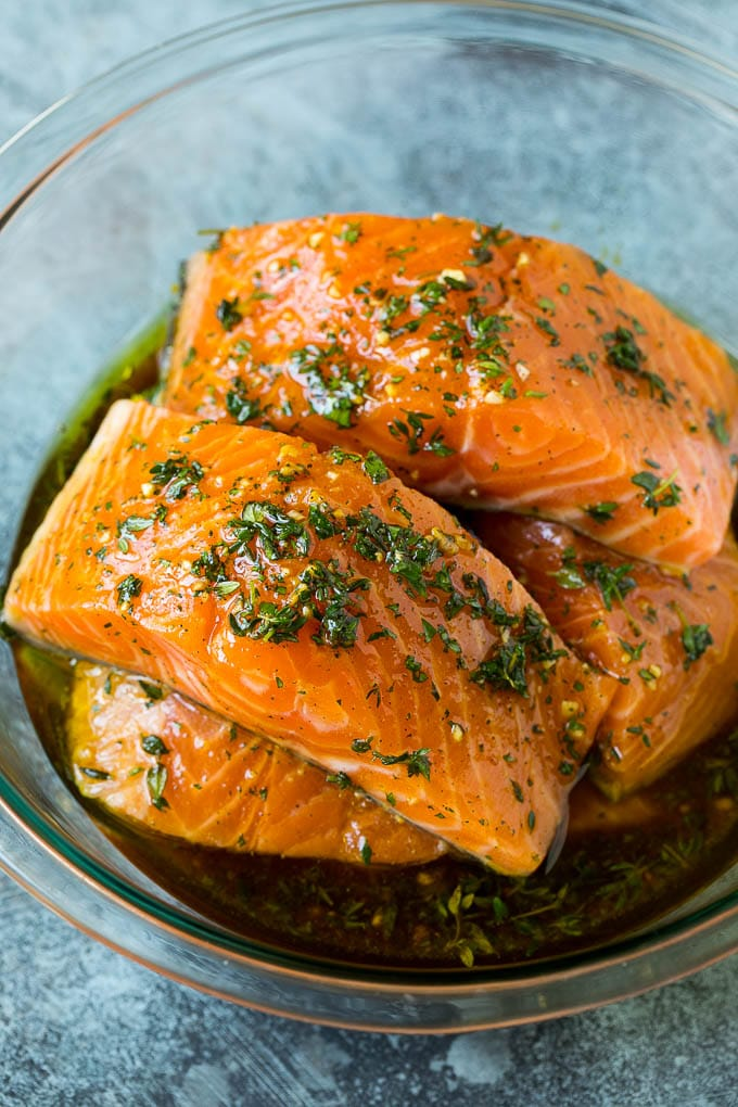 Salmon fillets in a bowl of olive oil, garlic and herbs.