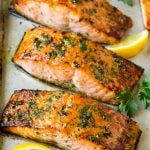 Broiled salmon with lemon wedges and parsley for garnish.