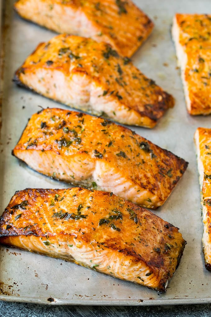 Cooked salmon fillets with herbs on top.