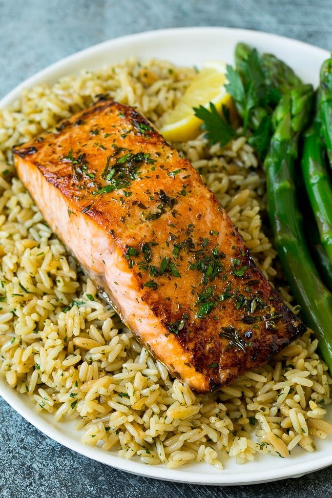 Broiled salmon served with rice and asparagus.