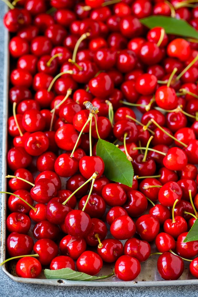 Fresh cherries spread out on a sheet pan.