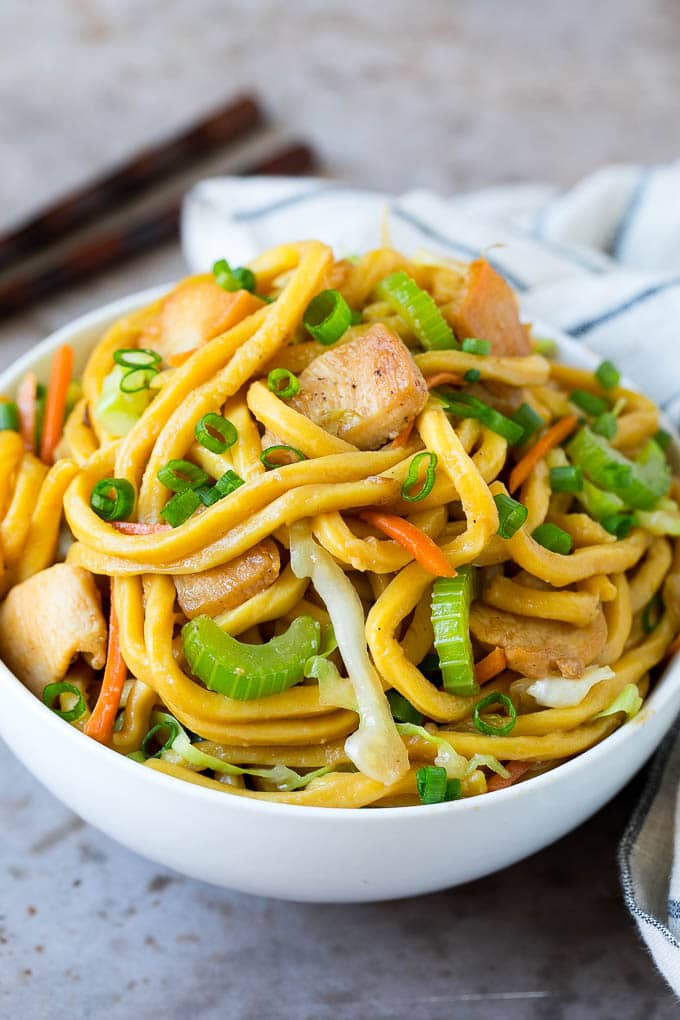 A bowl of chicken lo mein with noodles and vegetables.
