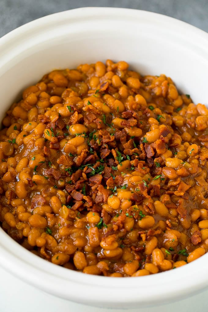 Slow cooker baked beans topped with bacon and parsley.