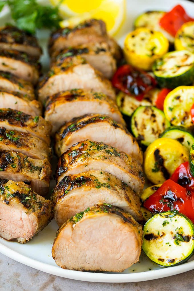 Grilled pork tenderloin on a serving plate with grilled vegetables on the side.