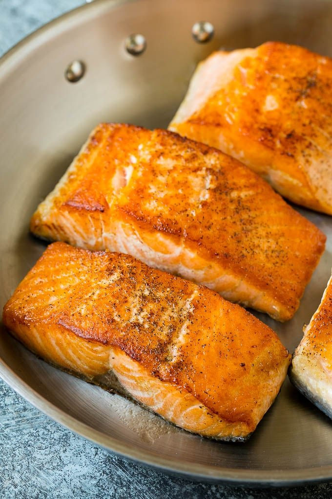 Seared salmon fillets in a pan.
