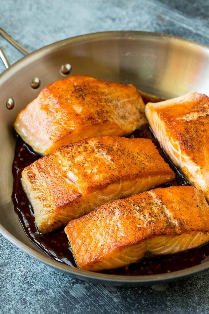 Salmon fillets sitting in honey glaze.