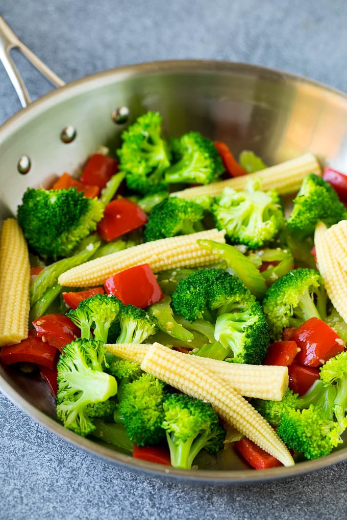 Broccoli florets, baby corn, bell peppers and celery in a skillet.