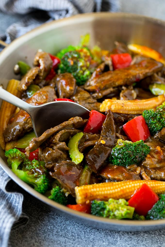 A serving spoon in a pan full of Hunan beef.