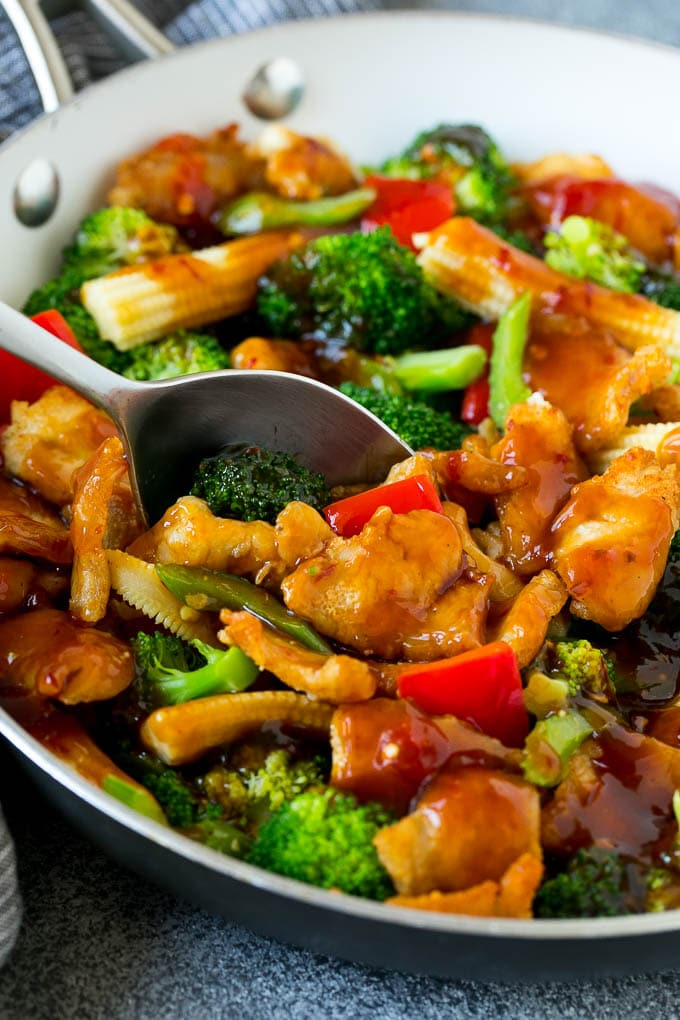A spoon serving up a portion of spicy chicken stir fry.