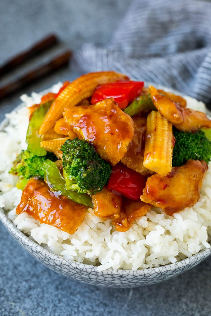 Hunan chicken with broccoli served over a bowl of rice.