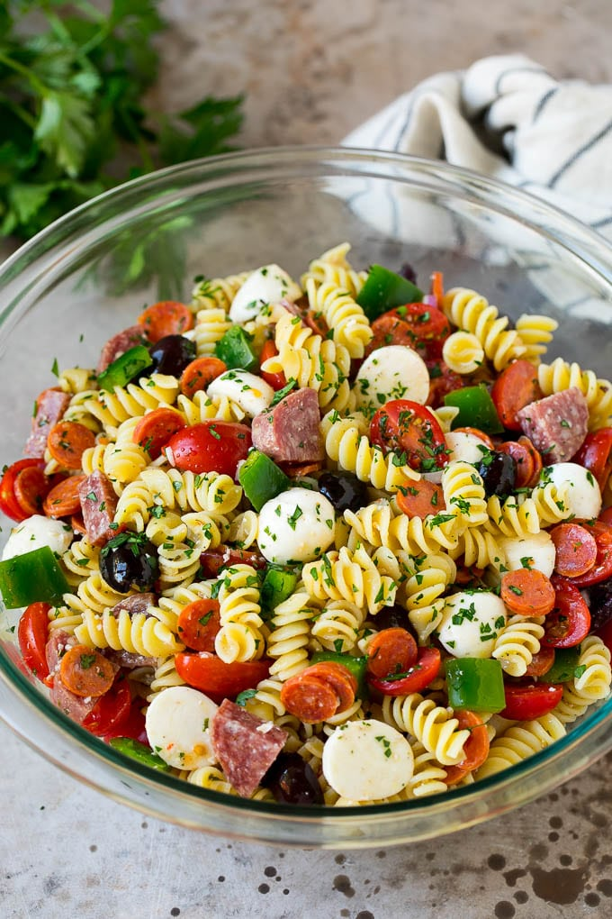 A bowl of Italian pasta salad filled with meats, cheese and vegetables.