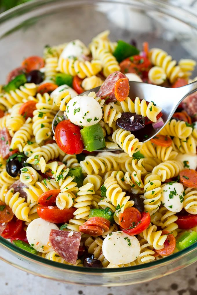 A serving spoon in a bowl of Italian style pasta salad.