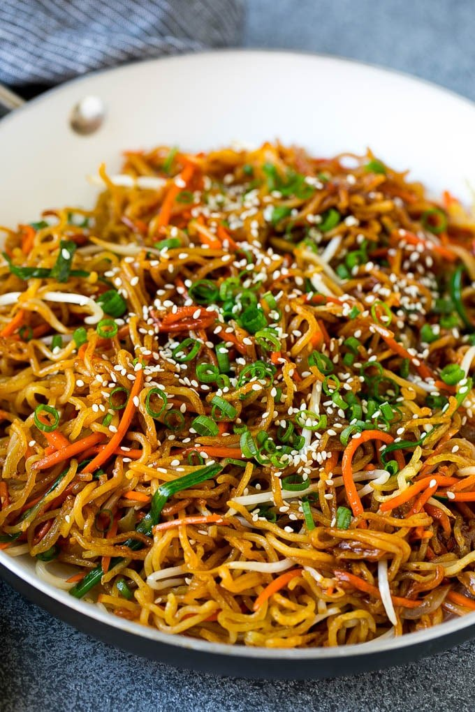 A skillet of pan fried noodles with carrots and bean sprouts.