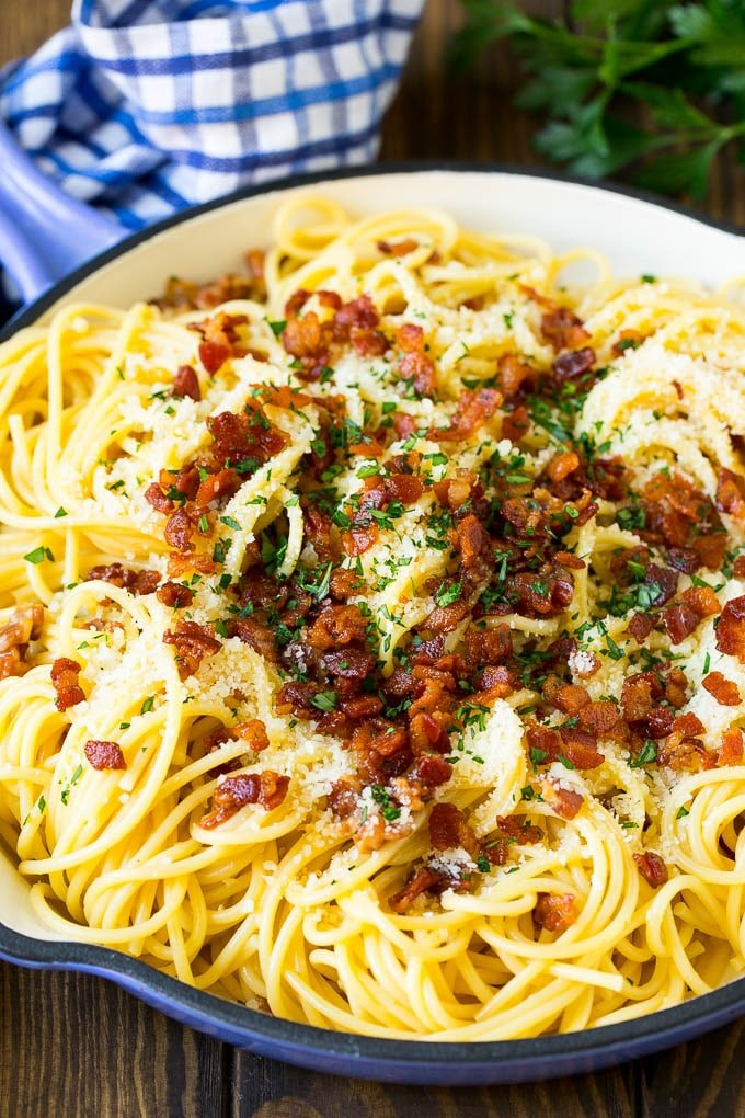 A skillet of pasta carbonara topped with bacon, parmesan cheese and parsley.