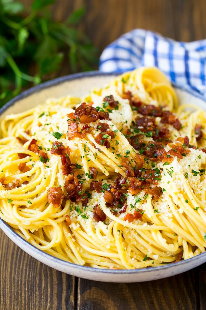 A bowl of carbonara pasta topped with bacon and cheese.